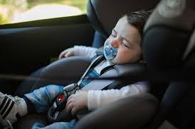 young child strapped into forward facing car seat