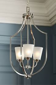 elegant long arms create symmetry in the transitional hanford hall foyer light by sea gull lighting tapered etched glass shades produce a soft uplight and