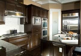 dark chocolate wood cabinetry surrounds white tile backsplash over dark tile flooring in this cozy kitchen