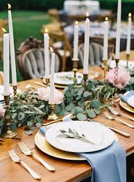 wedding table with gold and white plates with greenery in middle and cold candle holders