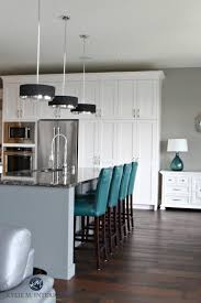 contemporary white kitchen with gray painted island in cambria ellesmere dark wood floors and sherwin