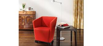 elegant red reading chair with black wood side-table with a pile of book  collections