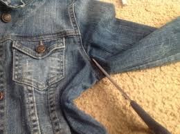 step one lay your jean jacket or denim shirt on a flat surface and begin to cut the sleeves off of both sides