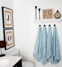 towel hooks. DIY Towel Hooks - Sew Ribbon Tabs On The Sides Of Towels So They Can Be
