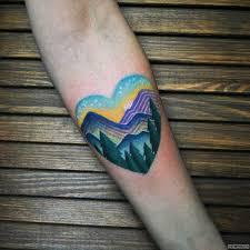 горы с елками в сердце тату на предплечье у девушки добавлено
