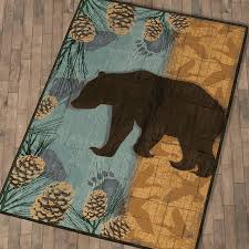 a black forest decor exclusive bear and moose are silhouetted over wildlife shadows and pinecone designs on these premium nylon rugs in turquoise beige