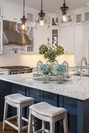 gorgeous kitchen with white cabinets glass globe pendants and navy island blue cabinet kitchen lighting
