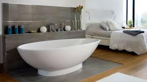 Bathroom. oval white acrylic bathtub and grey wooden shelf with faucet on  grey floor near