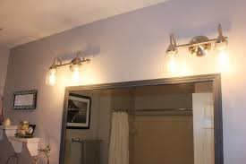 bathroom light fixtures with four yellow lamps and gold grab bars ideas