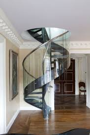 A spiral staircase of molded glass, resin, and stainless steel designed by  Bunny Williams connects the main living area of an apartment on New York  City's ...