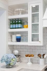 glass front cabinet next to floating shelves