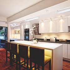 kitchen with white cabinetry under cabinet lighting and yellow under island bar lights