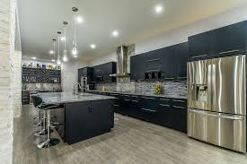 spacious kitchen with black cabinets stainless appliances tile backsplash and super white marble countertops
