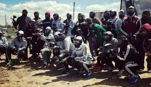 large group of paintball players sed in rows standing and kneeling to pose for a picture