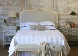 custom upholstered headboards with white bedding before the rustic wall  plus nightstand with table standing lamp