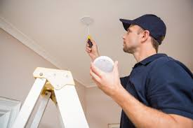 Electrician Installing Smoke Detector In Home