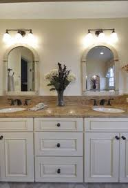 white bathroom cabinets with bronze hardware. beautiful bathrooms in va and md the gracefully arched mirrors are topped with lighting by mirabelle oil rubbed bronze. cabinetry is madura white bathroom cabinets bronze hardware b