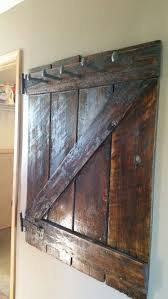100 year old barn door made into a coat rack using railroad spikes