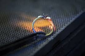a jeweller works on a ring in an ethical gold jewellery work in paris on february