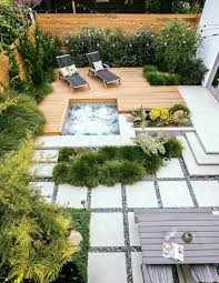 this backyard was made for relaxation from the redwood deck and hot tub to the lush foilage that creates a tropical oasis a level change makes this small