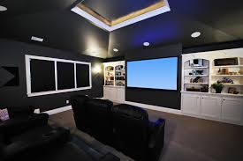 dark media room. The Black Walls And Furniture Of This Media Room Provide Sharp Contrast To White Built In Shelving Around Screen. Windows Have Out Shades Dark