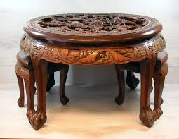ornately engraved round wooden table with two chairs side tables china first half