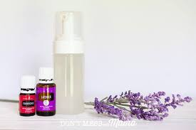 close up of essential oils pump bottle of face wash and lavender sprigs