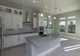 contemporary kitchen with white cabinets gray island counter pendant lighting and gray backsplash