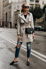 blonde woman wearing club monaco trench coat levis ripped jeans gucci black princetown mules chanel black