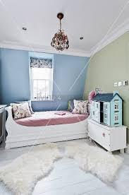 cheerful child s bedroom with large dolls house and soft animal skin rugs on floor