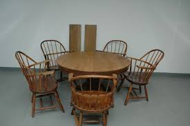 antique tiger oak pedestal table with carved claw feet 5 captain windsor style arm chairs not all matching table measures 48 x28 with no leaves