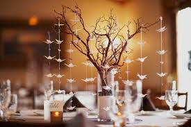 Wedding table setting with nature theme of bonsai tree and origami birds.