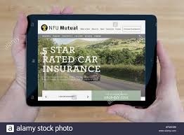a man looks at the nfu mutual website on his ipad tablet device shot against