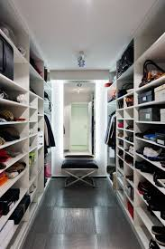 this white closet has a tiled floor a large mirror and is mostly shelves