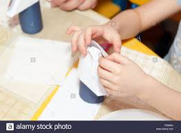 small child hands glue paper crafts at a school desk