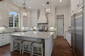 White kitchen with marble counters large dining island
