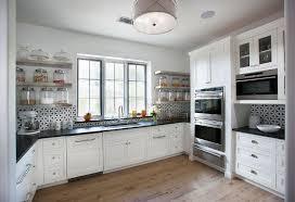 stainless steel floating kitchen shelves with black and white backsplash tiles