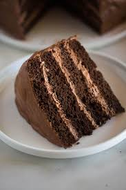 a slice of homemade chocolate cake with layers of chocolate mousse filling on a white