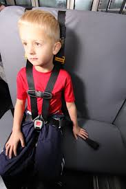 a boy sits on the school bus buckled into his sauard star