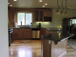 attractive unfinished wood kitchen hickory cabinets with black dark granite countertops and glossy wood floors in