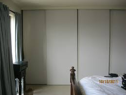 large white wooden sliding closet door connected by shabby grey