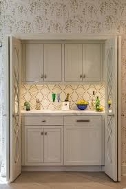 wet bar lighting. kitchen with gray mirrored folding doors opening to a hidden wet bar filled upper cabinets fitted under cabinet lighting and lower
