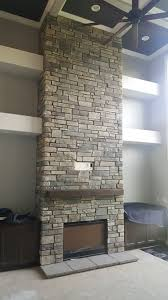 floor to ceiling stone veneer fireplace installation in lake country