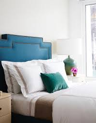 blue velvet headboard with white and brown hotel bedding