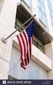 American Flag Waving Against Modern Office Building Stock Photo