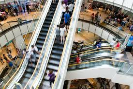 people in motion in escalators at the modern shopping mall stock