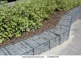 Modern Gabion fence with stones in wire mesh. Gabion wire mesh fencing with  natural stones
