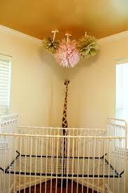 pink gold tissue paper pom poms above white iron crib and giraffe statue