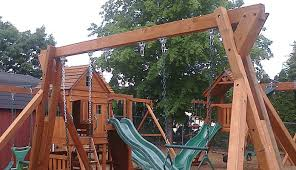 a wooden swing set with a playhouse and slide all thumbs diy