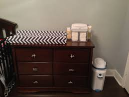 Kids Room. brown patterned pad Changing Table Topper on over brown wooden  Dresser with drawer